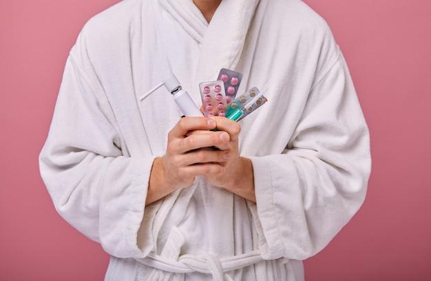 Hombre en bata blanca con un inhalador en una mano y pastillas y jeringas en segunda