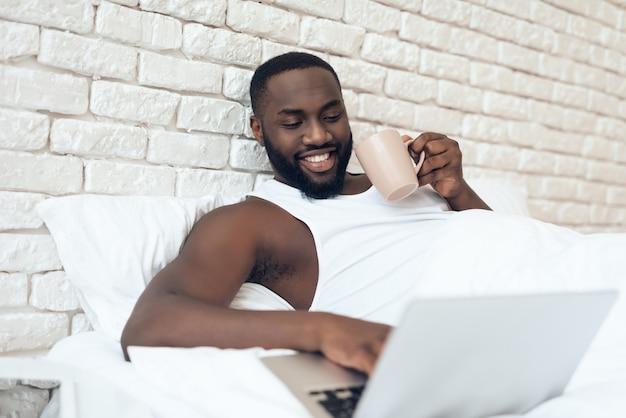 Hombre bebe café en la cama mientras trabaja con el portátil.