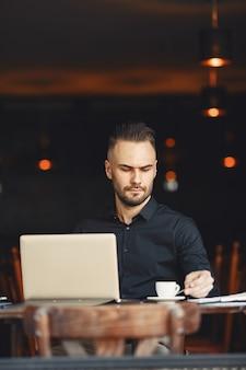 El hombre bebe café. el hombre de negocios lee documentos. director con camiseta.