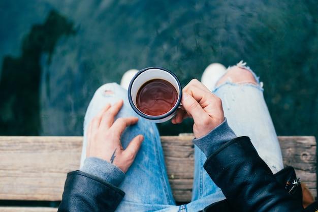 El hombre bebe café de la taza de esmalte al aire libre