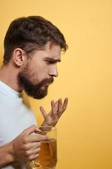 Un hombre bebe cerveza de un vaso y come comida chatarra frita