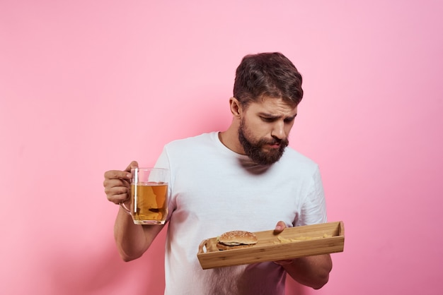 Un hombre bebe cerveza de un vaso y come comida chatarra