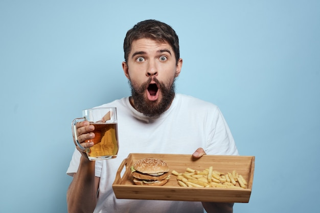 Un hombre bebe cerveza de un vaso y come comida rápida frita chatarra