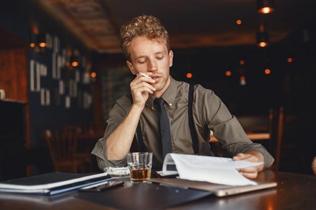 El hombre bebe whisky. el hombre de negocios lee documentos. director con camiseta y tirantes. Foto gratis