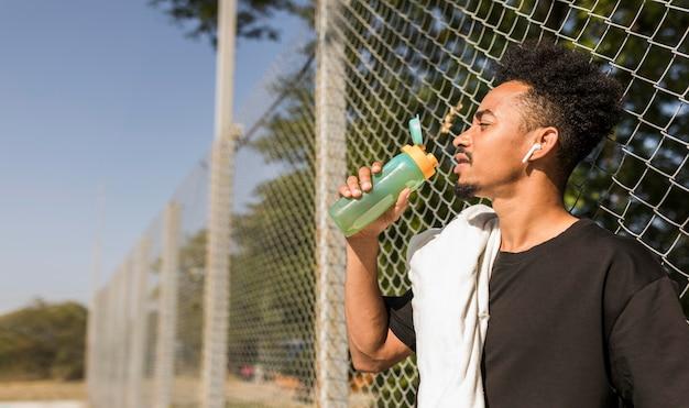 Hombre bebiendo agua después de un partido de baloncesto