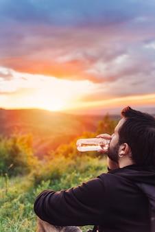 Hombre bebiendo agua y disfrutando del atardecer de montaña