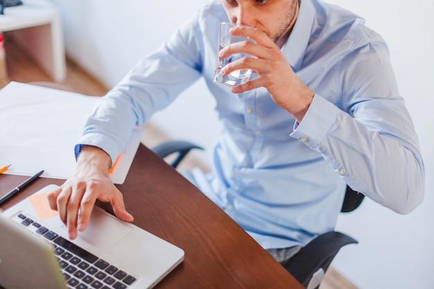Hombre bebiendo agua sentada a la mesa