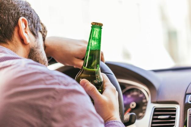 Hombre bebiendo alcohol mientras conduce el auto