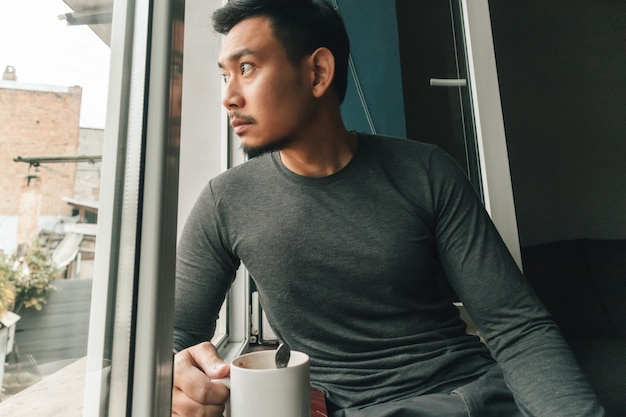El hombre está bebiendo café caliente y siente relajarse junto a las ventanas.