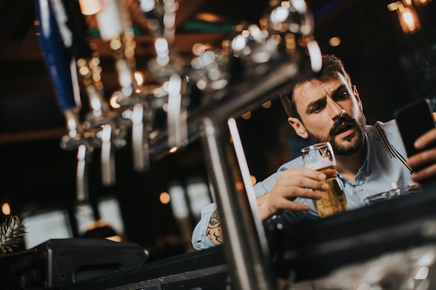 Hombre bebiendo cerveza, fumando cigarrillos y usando el teléfono móvil en el pub