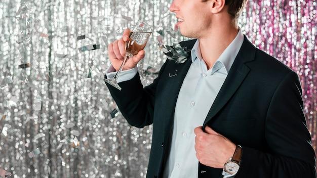 Hombre bebiendo champán en fiesta de año nuevo