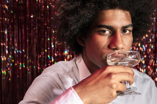 Hombre bebiendo una copa de champán con cortina de destellos en segundo plano.