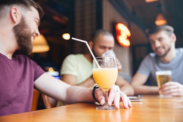 Hombre bebiendo jugo de naranja mientras amigos bebiendo cerveza en el pub
