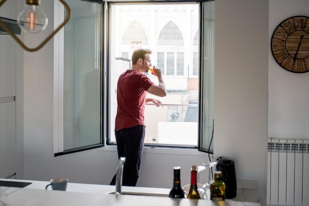 Hombre bebiendo jugo de naranja por las ventanas