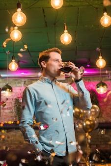 Hombre bebiendo vino en una fiesta en el bar