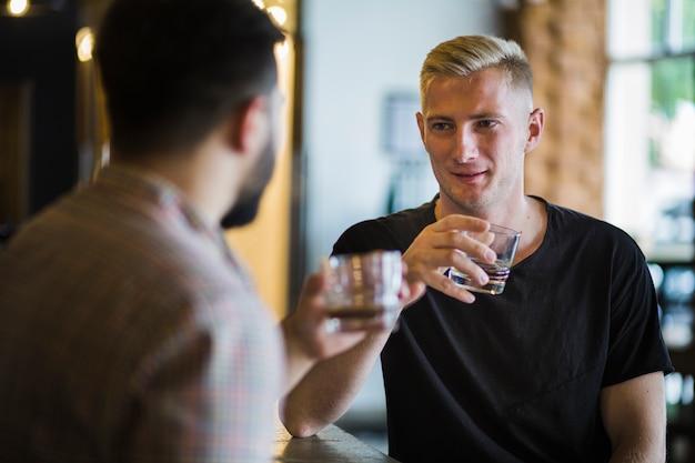 Hombre bebiendo whisky con su amigo en el bar