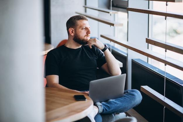 Hombre de beraded trabajando en una computadora portátil en un café