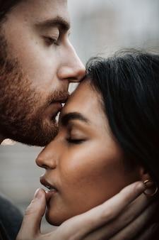 Hombre besa a joven india tierna y apasionada sosteniendo su i