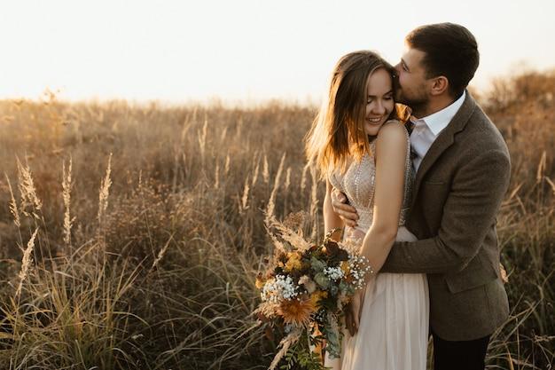 Un hombre besa a su esposa. ella ríe.