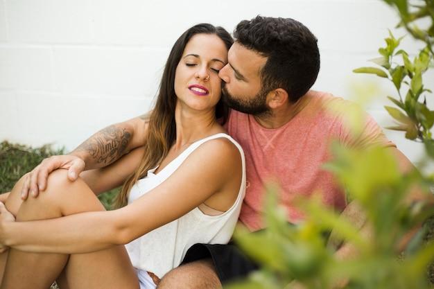 Hombre besando a su bella esposa al aire libre