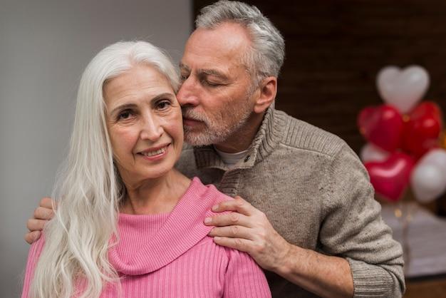 Hombre besando a la esposa en la mejilla el día de san valentín