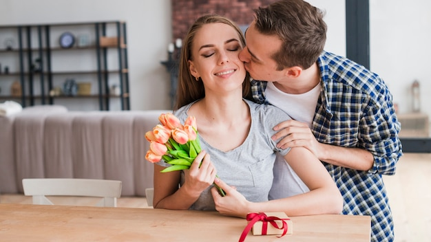 Hombre besando feliz esposa y dando regalos