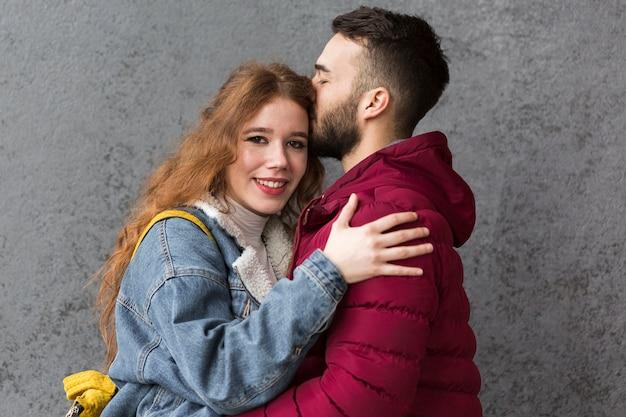 Hombre besando feliz novia hermosa