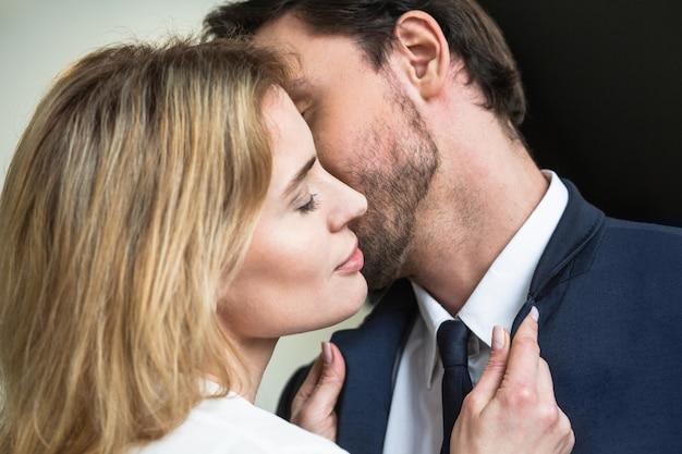 Hombre besando a una mujer bonita rubia de pie con los ojos cerrados en primer plano