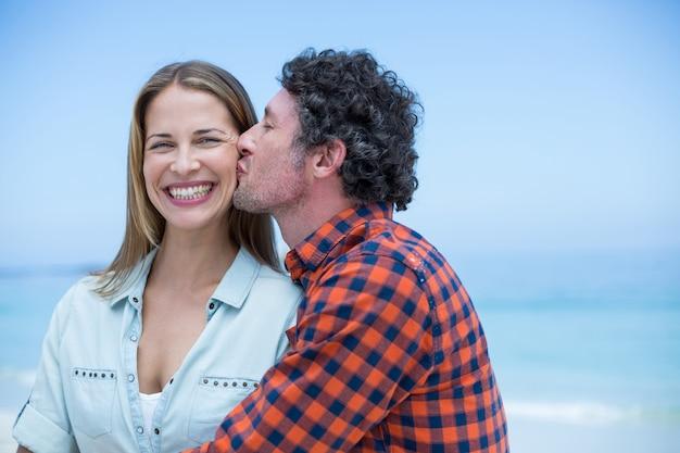 Hombre besando a mujer feliz en la orilla del mar