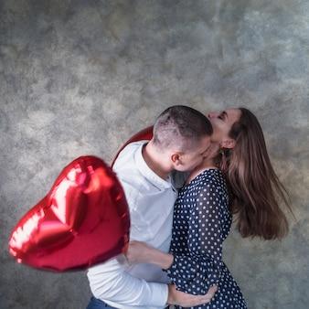 Hombre besando a mujer con globos de corazón
