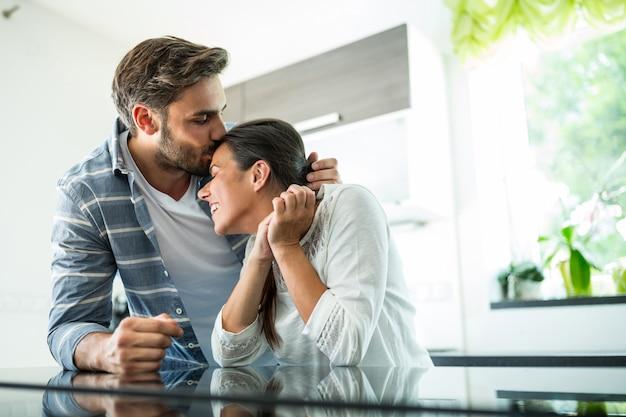 Hombre besándose en la frente de mujer