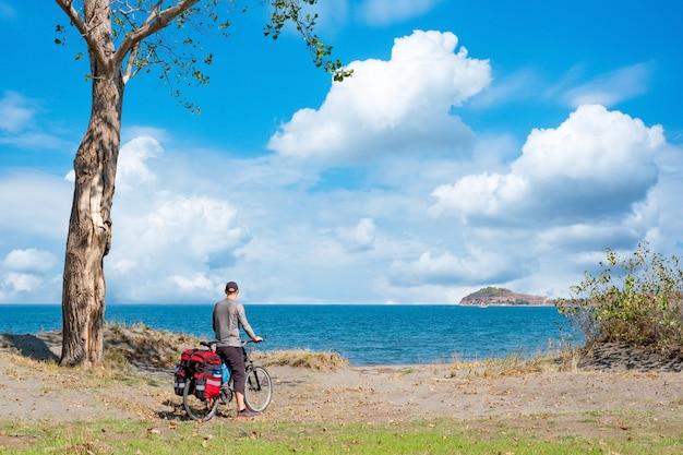 Hombre en una bicicleta de montaña con una mochila grande con vistas al mar negro en bulgaria