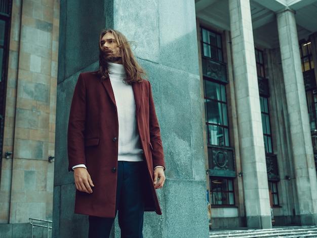 Hombre bien vestido confiado hermoso con la barba que presenta al aire libre que mira lejos. modelo masculino rico de moda en abrigo de invierno rojo y suéter blanco