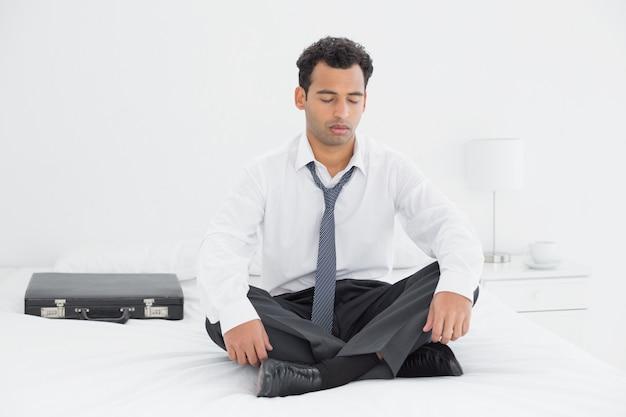 Hombre bien vestido sentado con los ojos cerrados en la cama en casa