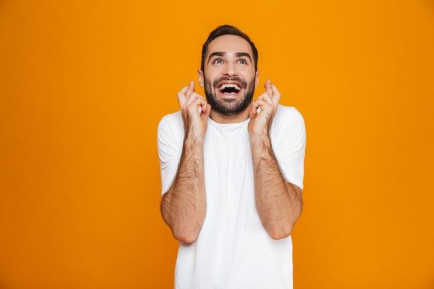 Hombre con bigote en camiseta apretando los puños mientras está de pie, aislado en amarillo