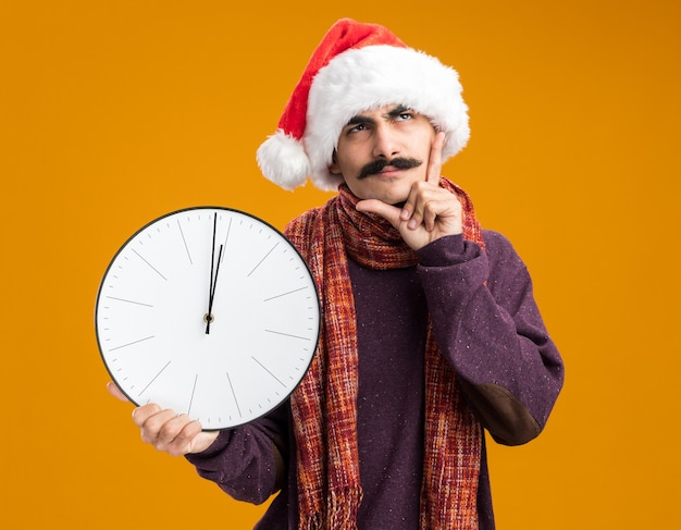 Hombre bigotudo vestido con gorro de papá noel de navidad con cálida bufanda alrededor de su cuello sosteniendo el reloj mirando hacia arriba desconcertado parado sobre la pared naranja
