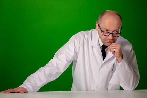 Hombre blanco con una bata blanca de laboratorio, gafas, sobre un fondo verde