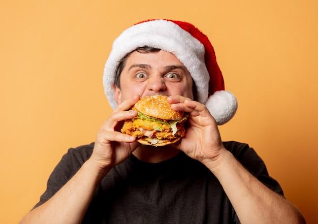 Hombre blanco en camiseta negra y gorro de papá noel con hamburguesa en pared amarilla