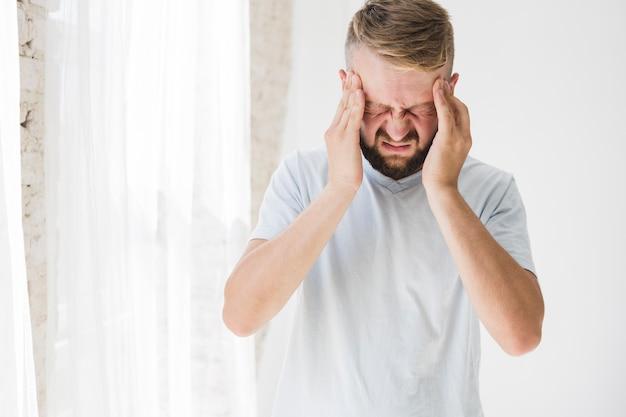 Hombre de blanco que sufre de dolor.