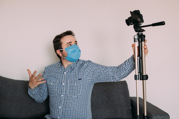 Hombre blogger en máscara médica habla sobre coronavirus. el video de grabación de man cuenta cómo protegerse del 2019-ncov. blogger habla a mers-cov sobre el uso de toallitas con alcohol y termómetro