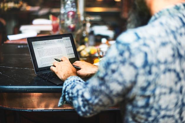Un hombre blogueando en un bar