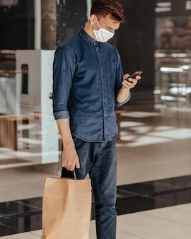 Hombre con una bolsa de compras leyendo un mensaje en su teléfono inteligente. concepto de protección de la salud.