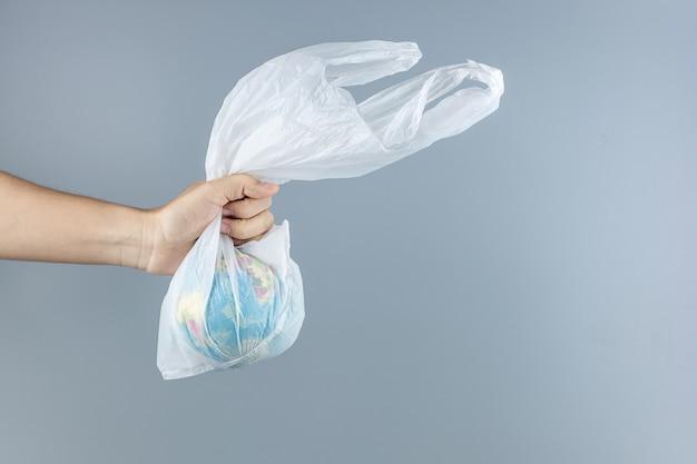 Hombre con bolsa de plástico y globo interior con espacio de copia de texto. protección del medio ambiente, cero residuos, reutilizable, decir no plástico, concepto del día mundial del medio ambiente y del día de la tierra