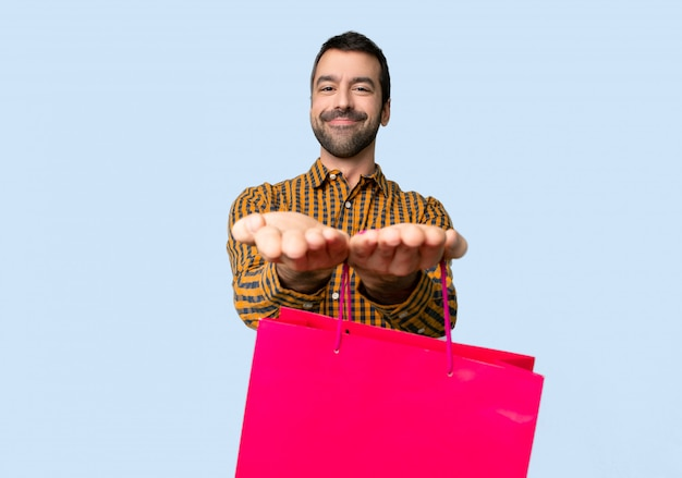 Hombre con bolsas de compra con copyspace imaginario en la palma para insertar un anuncio sobre fondo azul aislado