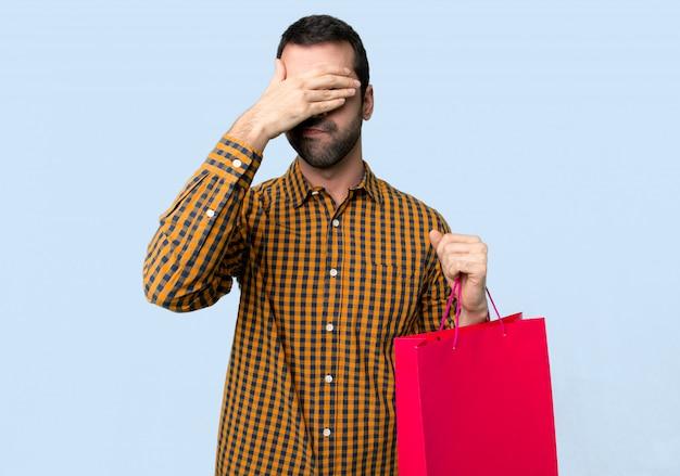 Hombre con bolsas de compra cubriendo los ojos con las manos. no quiero ver algo sobre fondo azul aislado