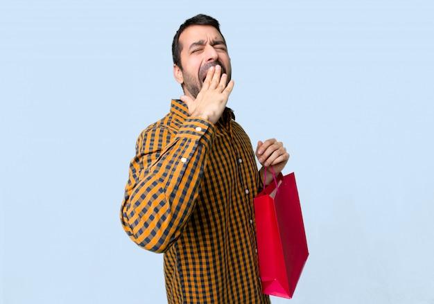 Hombre con bolsas de compras bostezando y cubriendo la boca abierta con la mano sobre fondo azul aislado