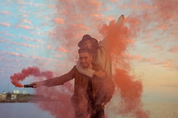 Hombre con bomba de humo rojo sosteniendo a mujer en la espalda