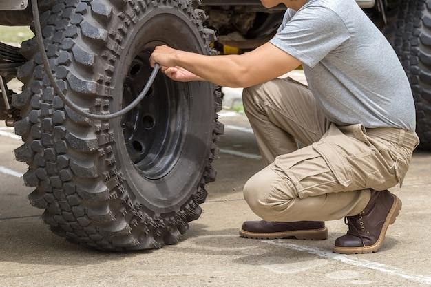 El hombre bombea una rueda de coche offroad con un compresor.