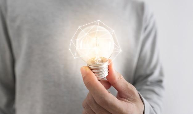 Un hombre con bombilla incandescente. nuevas ideas, innovación, redes y conceptos de ahorro de energía.