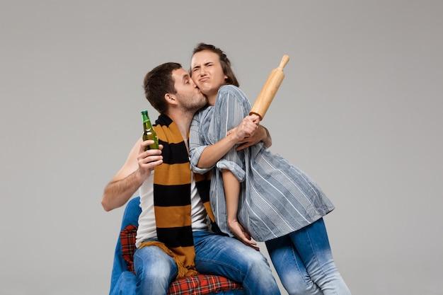 Hombre borracho besando a esposa disgustada, sosteniendo cerveza sobre pared gris